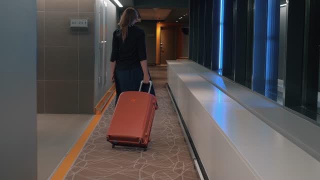 woman with trolley case in the hotel hallway - hotel checkin video stock e b–roll