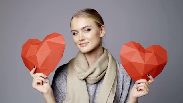 frau mit zwei roten low-poly papier herzformen - woman and polygon stock-videos und b-roll-filmmaterial
