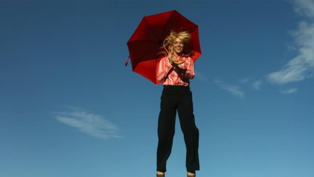 vídeos de stock e filmes b-roll de mulher com guarda-chuva salta no ar, câmara lenta - guarda chuva