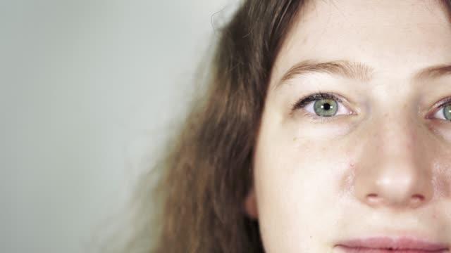 目の下のバッグを持つ女性。目のバッグを示す女の子のふくらんだ目。女性の目のクローズアップ - まぶた点の映像素材/bロール