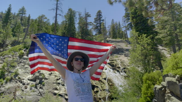Woman with US flag. Waterfall on the background.