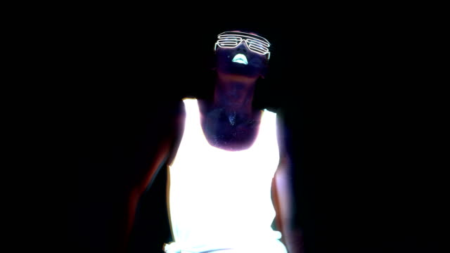 woman with uv face paint, glowing clothing, glowing glasses, bracelet dancing in front of camera, half body shot. asian woman. glitch effect. women. - seduzione video stock e b–roll