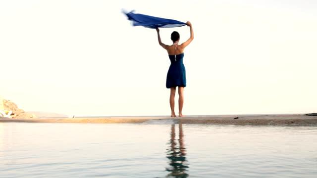 woman with waving sarong at the beach - sarong bildbanksvideor och videomaterial från bakom kulisserna