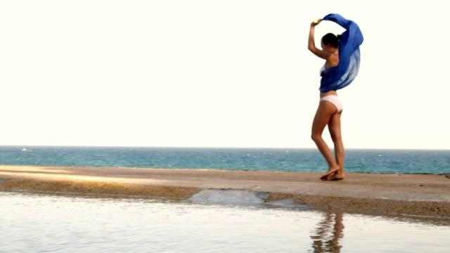 Woman with waving sarong walking on the seashore, slow motion video
