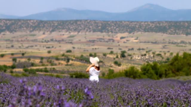 Woman with white dress and white hat standing and looking around on lavender field in Isparta, Turkey