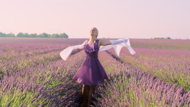 WA Woman with white scarf spinning in a field of lavender Wide angle shot of a mid adult woman with white scarf spinning in the middle of a lavender field. Plateau De Valensole. Provence-Alpes-Cote d'Azur. France. Shoot in 8K resolution. provence alpes cote d'azur stock videos & royalty-free footage