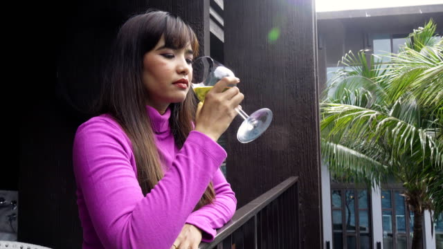 Woman with wine glass using cell when relaxing in the balcony