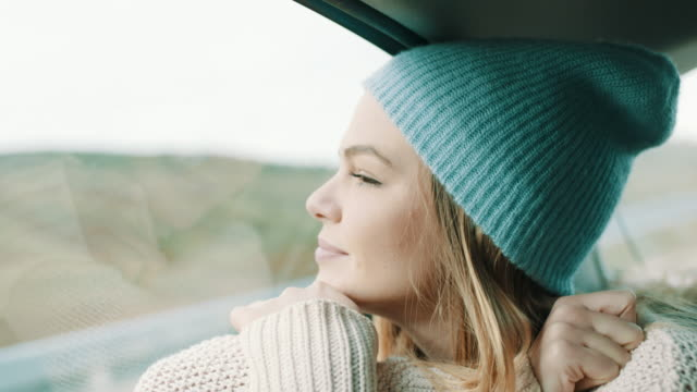woman with winter cap on her head looking outside through the window at nature from back seat of the car - guardare il paesaggio video stock e b–roll