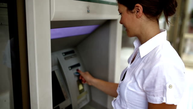 woman withdrawing money at the atm - banks and atms stock videos & royalty-free footage