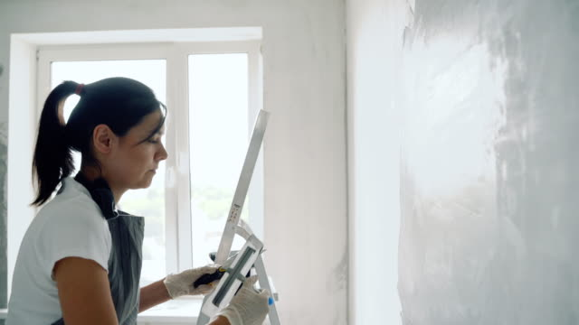 Woman worker using a spatula painting walls in the apartment or house.