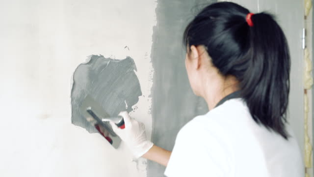 Woman worker using a spatula painting walls in the apartment or house. Focus on hands