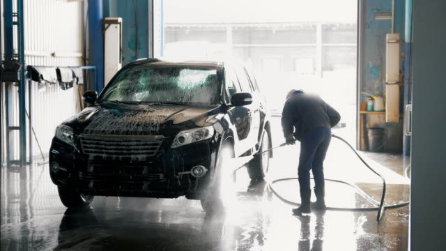 woman worker with the water hose in car-washing facility - struttura pubblica video stock e b–roll