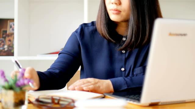 女性作業、ノート パソコンのキーボードは在宅勤務で入力 - マルチタスク点の映像素材/bロール