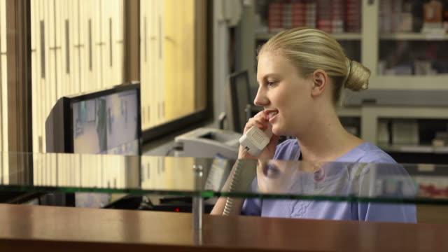 woman working as nurse in clinic and speaking on telephone - vårdklinik bildbanksvideor och videomaterial från bakom kulisserna