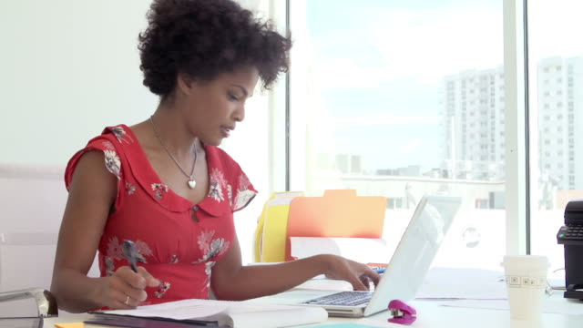 Woman Working At Desk In Design Studio Answering Phone
