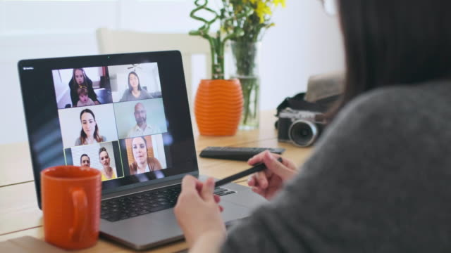 Woman Working at Home on a Web Chat Meeting A woman working at home participating in a online web meeting. zoom call stock videos & royalty-free footage