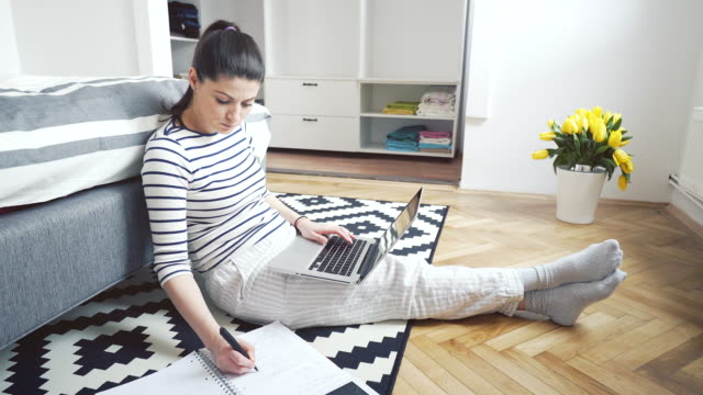 Woman working at home using a laptop. video
