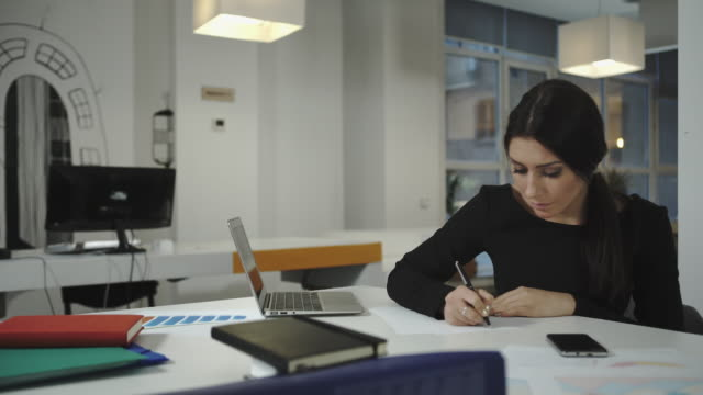 A woman working at the computer, taking notes on a sheet, crumples and throws video