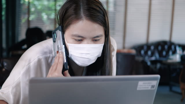 woman working by smartphone and protection from coronavirus and pm2.5 dust by mask in office/public places - mask surgery video stock e b–roll