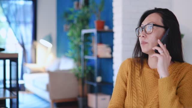 kvinna som arbetar från hemmakontoret - använda telefon bildbanksvideor och videomaterial från bakom kulisserna