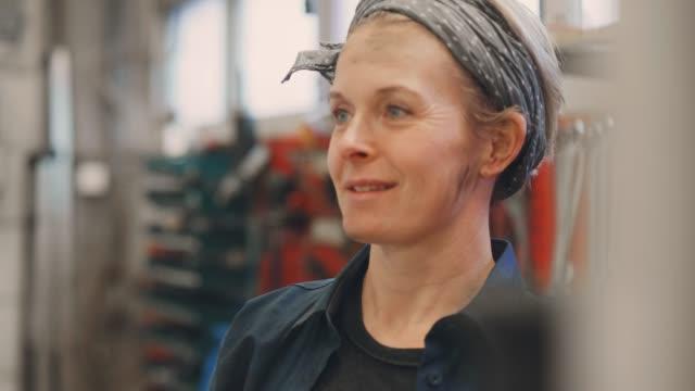 donna che lavora in un'officina di riparazione - artigiano video stock e b–roll