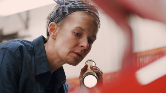 Woman working in an auto repair workshop A confident and skilful woman is working alone in an auto repair shop. Handheld shot in 4K resolution. flashlight stock videos & royalty-free footage