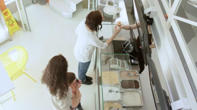 vidéos et rushes de femme travaillant dans une cafétéria qui dessert gâteau de cheminée à un client au comptoir - pâtisseries et feuilletés