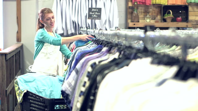 Woman working in clothing store, putting clothes on rack video