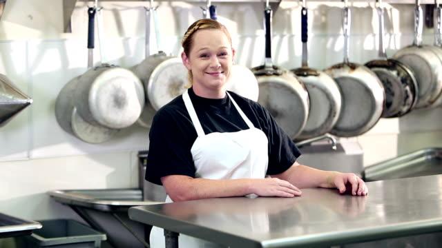 vídeos de stock e filmes b-roll de woman working in commercial kitchen - avental