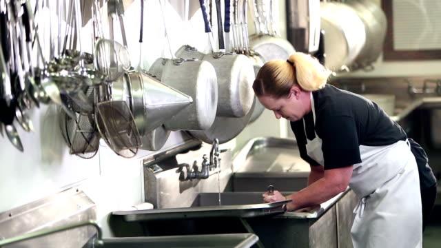 vídeos de stock e filmes b-roll de woman working in commercial kitchen washing pots - avental