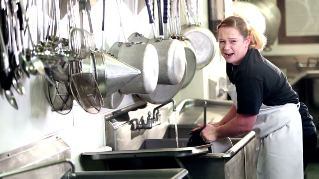 Woman working in commercial kitchen washing pots A mid adult woman in her 30s working in a commercial kitchen scrubbing pots and pans in the sink. She looks up at the camera, talking as she continues to wash. kitchen sink stock videos & royalty-free footage