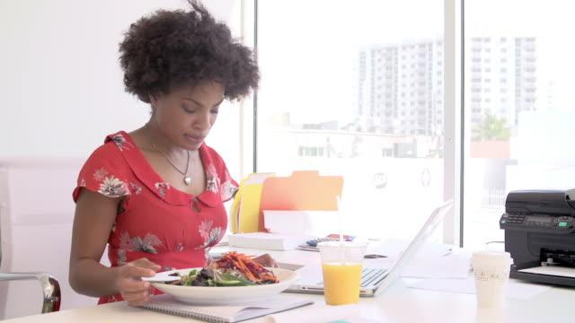 frau arbeitet im design-studio musik, mittagessen am schreibtisch - salat speisen stock-videos und b-roll-filmmaterial