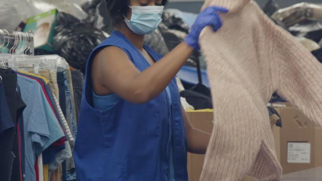 donna che lavora in centro donazioni ordina abiti donati - abbigliamento video stock e b–roll