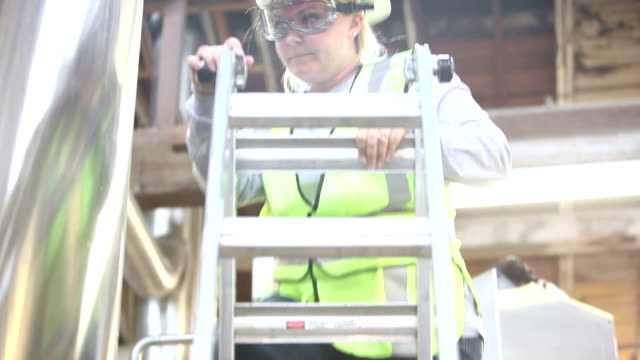 Woman working in factory climbing ladder by storage tank video
