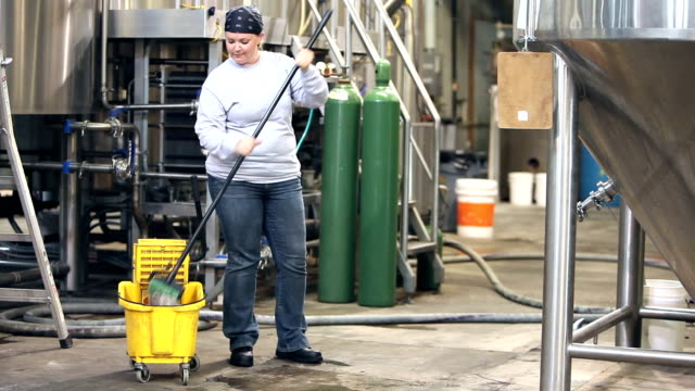 Woman working in factory, mopping floor video