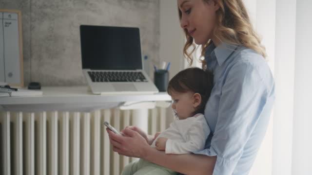 4 K : Femme travaillant dans le bureau à domicile avec son bébé - Vidéo