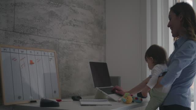 4 K  : ホームオフィスで働く女性彼女の赤ちゃん ビデオ