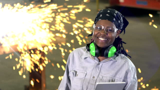Woman working in metal fabrication shop, with welder A young woman working in a metal fabrication shop, on the factory floor, a welder working in the background. The African-American woman is in her 20s, holding a digital tablet, smiling at the camera. metalwork stock videos & royalty-free footage