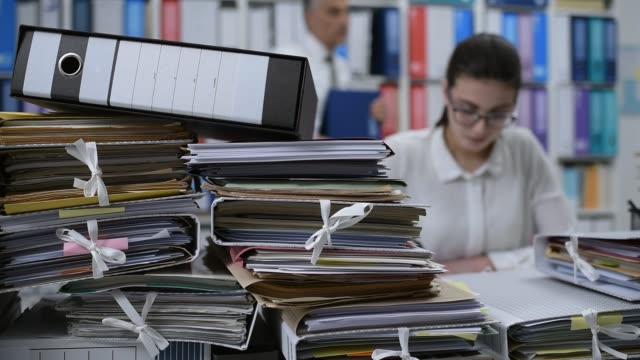 Woman working in the office Woman working in the office and calculating business balances, the desktop is full of paperwork: accounting and management concept accounting stock videos & royalty-free footage