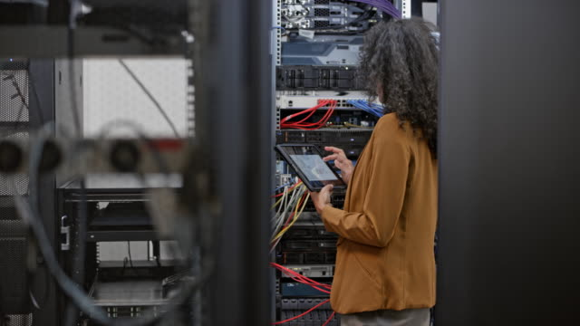 DS Woman working in the server room with a digital tablet Medium dolly shot of a female technician supervising the servers in the server room with a digital tablet in her hand. server room stock videos & royalty-free footage