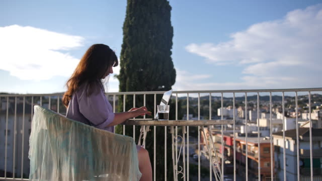 woman working on a laptop on the balcony