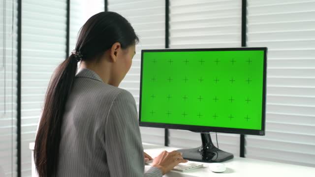 近代的なオフィスに緑色の画面でコンピューターで働く女性 ビデオ