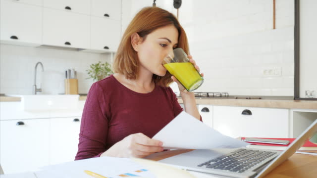 Woman working on finances. Woman working remotely from the comfort of her home. She is preparing new reports and analzying new ideas for cost efficiency. orange juice stock videos & royalty-free footage