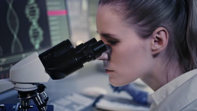 woman working on laboratory equipment. dna research on computer screens - генетическое исследование стоковые видео и кадры b-roll