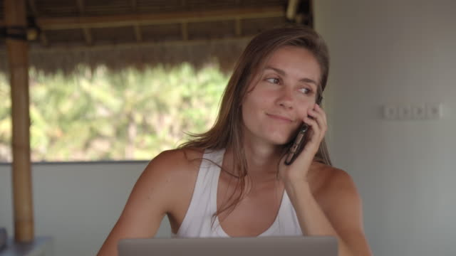 Woman Working on Laptop and Answering Phone Call in Thatched Patio Young tanned Caucasian woman working on laptop, answering phone call and taking notes during conversation while doing remote job in thatched tropical patio minority groups stock videos & royalty-free footage