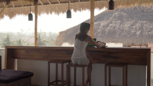 Woman Working on Laptop and Writing in Notepad in Tropical Patio Arc shot of young tanned woman using laptop and taking notes while working remotely in thatched patio in tropical country minority groups stock videos & royalty-free footage
