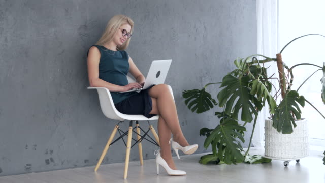 Woman working on laptop at office Beautiful young businesswoman working on laptop at office cross legged stock videos & royalty-free footage