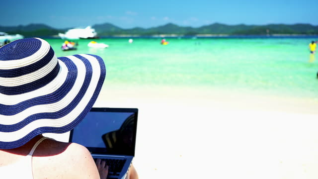 Woman working on the beach by typing her laptop. video