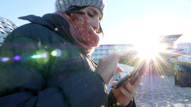 Woman working on the go Woman alone uses the ipad to solve some problems at work, while enjoying holidays at the beach, exactly in the German Ostsee, in a cold winter day daylight savings stock videos & royalty-free footage