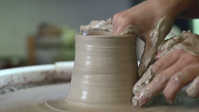 vídeos de stock, filmes e b-roll de mulher que trabalha na roda do oleiro. as mãos esculpe um copo do potenciômetro de argila. - cerâmica artesanato